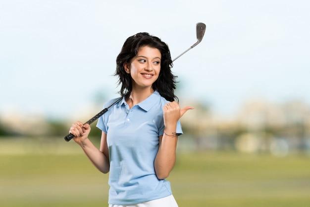 Giovane donna del giocatore di golf che indica il lato per presentare un prodotto all'aperto