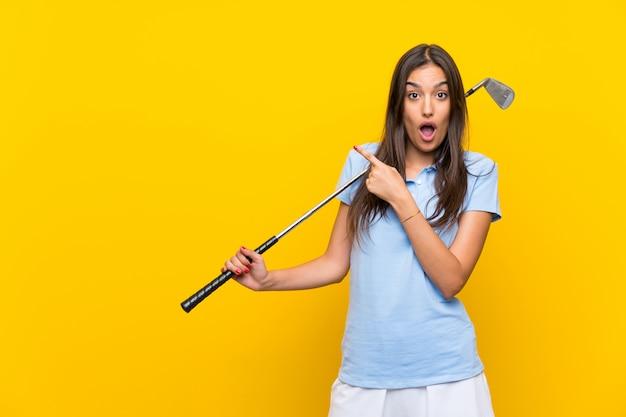 Giovane donna del giocatore di golf isolata sul lato sorpreso e indicante della parete gialla