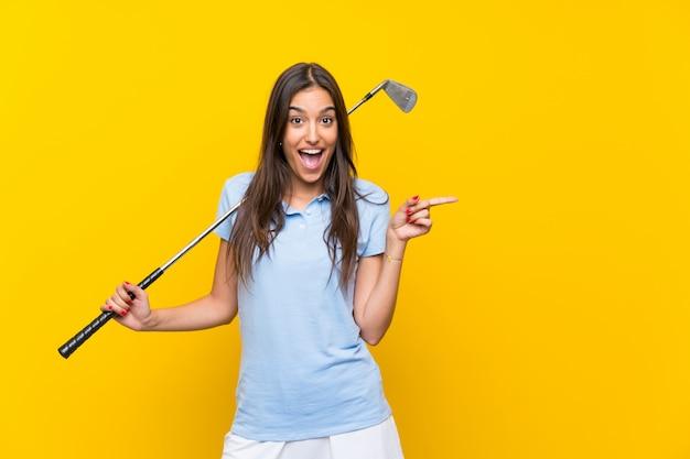 Giovane donna del giocatore di golf isolata sulla parete gialla sorpresa e che indica barretta il lato