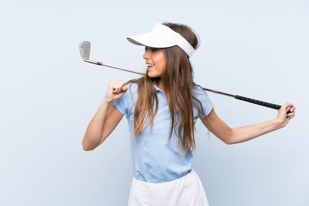Giovane donna del giocatore di golf sopra la parete blu isolata