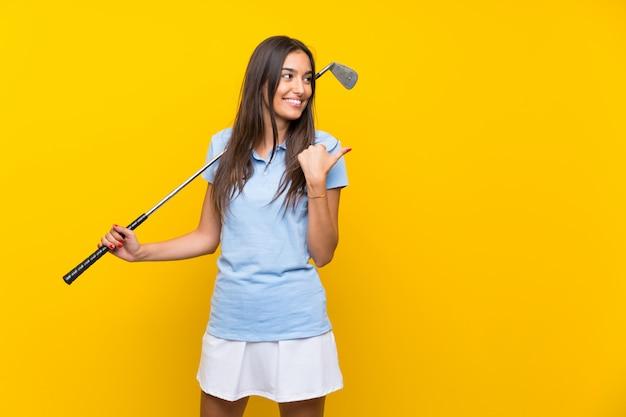 Giovane donna del giocatore di golf sopra la parete gialla isolata che indica il lato per presentare un prodotto