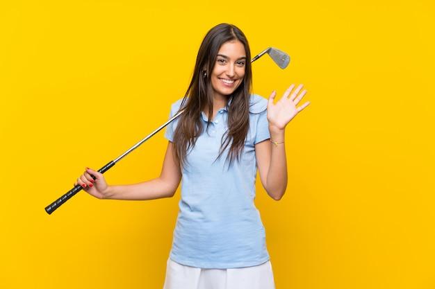 Giovane donna del giocatore di golf sopra la parete gialla isolata che saluta con la mano con l'espressione felice