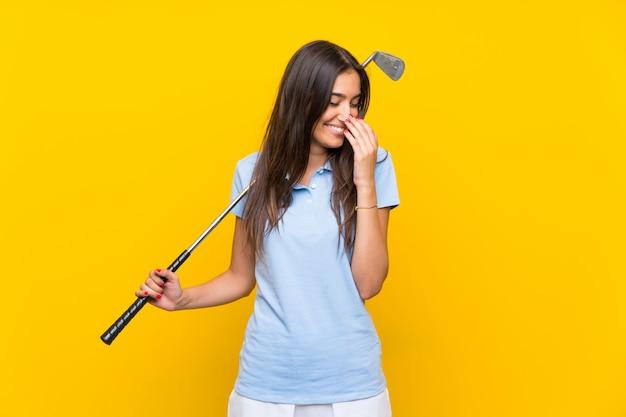 Giovane donna del giocatore di golf sopra la parete gialla isolata che sorride molto