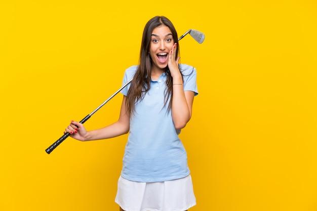 Giovane donna del giocatore di golf sopra la parete gialla isolata con espressione facciale sorpresa e colpita