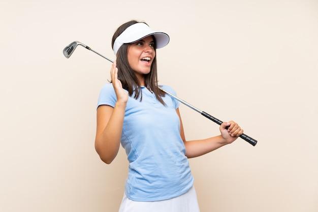 Giovane donna del giocatore di golf sopra la parete isolata con espressione facciale di sorpresa