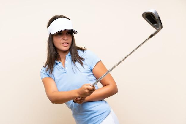 Giovane donna del giocatore di golf sopra la parete isolata