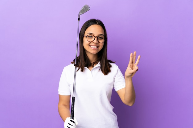 Giovane donna del giocatore di golf sopra la parete variopinta felice e contando tre con le dita