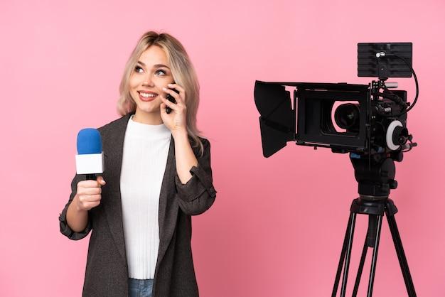 Giovane donna del giornalista sopra la parete isolata