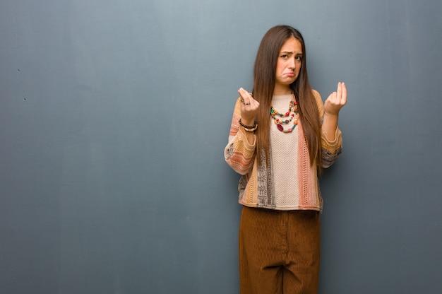 Giovane donna del hippie che fa un gesto di bisogno