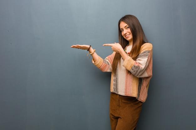 Giovane donna del hippie che tiene qualcosa con la mano