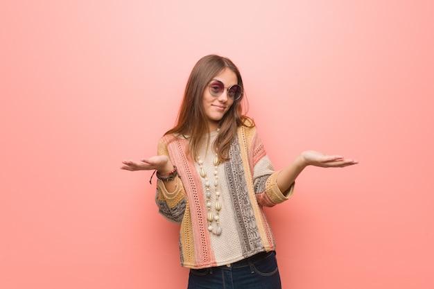 Giovane donna del hippie su fondo rosa confuso e dubbioso