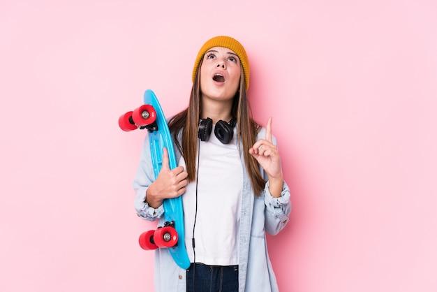 Giovane donna del pattinatore che tiene un pattino che indica parte superiore con la bocca aperta.
