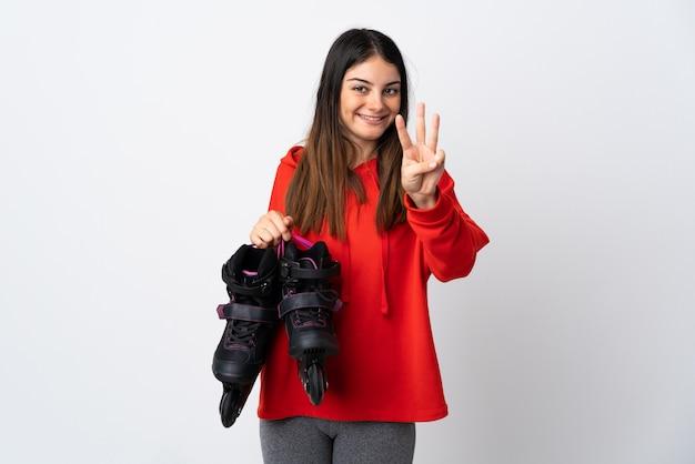 Giovane donna del pattinatore isolata su bianco felice e contando tre con le dita