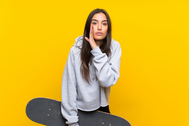 Giovane donna del pattinatore sopra la parete gialla isolata che bisbiglia qualcosa