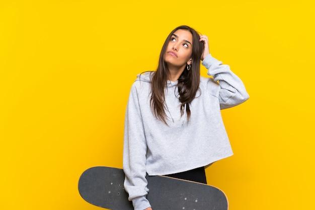 Giovane donna del pattinatore sopra la parete gialla isolata che ha dubbi e con l'espressione confusa del fronte