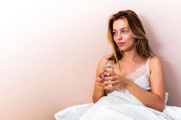 Giovane donna del primo piano che distoglie lo sguardo tenendo un bicchiere d'acqua a letto