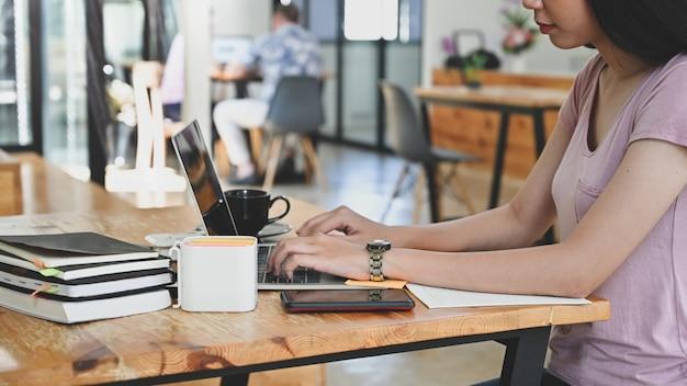 Giovane donna del primo piano che lavora con il computer portatile sullo spazio rannicchiato.