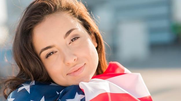 Giovane donna del primo piano che tiene la grande bandiera degli sua
