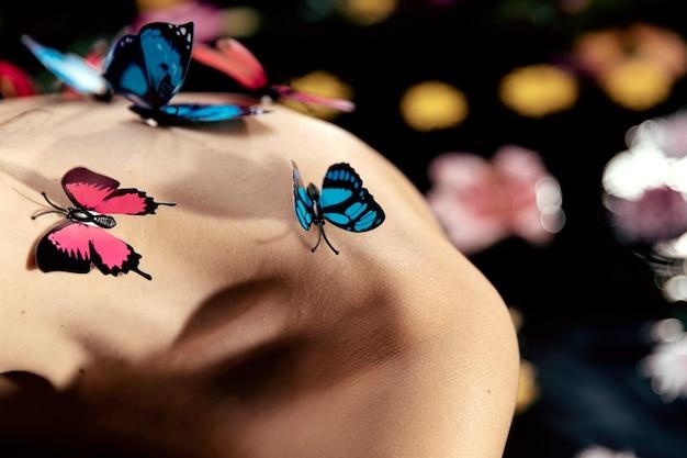 Giovane donna del primo piano con le farfalle sulla cima