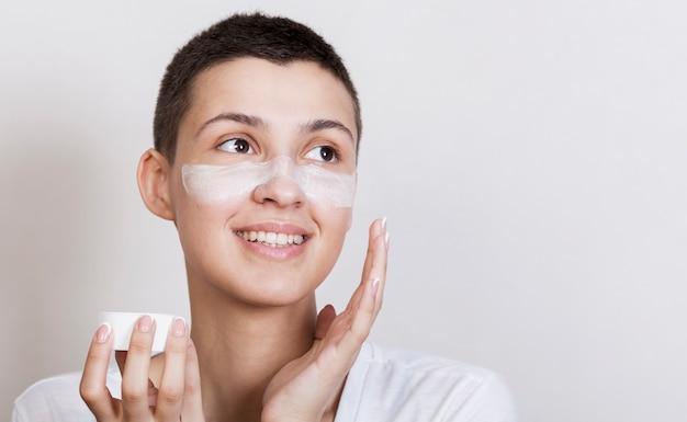 Giovane donna del ritratto che applica crema sul fronte