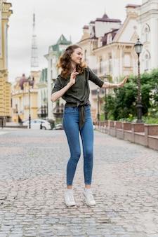 Giovane donna del ritratto che balla sulla via