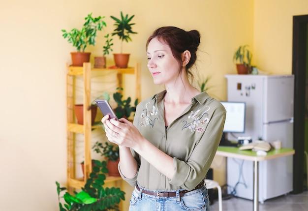 Giovane donna del ritratto che manda un sms facendo uso dello smart phone
