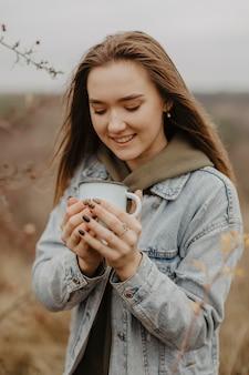 Giovane donna del ritratto che tiene tazza con tè