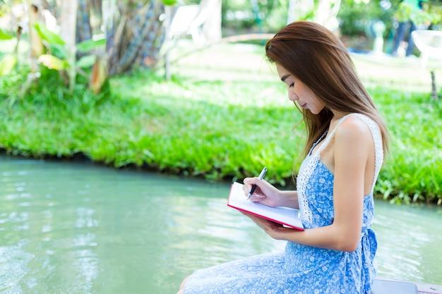Giovane donna del ritratto con il diario in parco