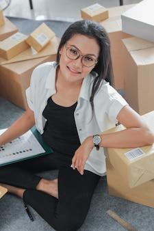 Giovane donna del ritratto con l'affare online che lavora a casa
