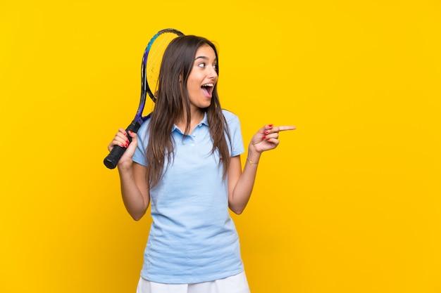 Giovane donna del tennis sopra la parete gialla isolata sorpresa e che indica dito il lato