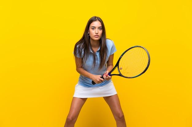 Giovane donna del tennis sopra la parete gialla isolata
