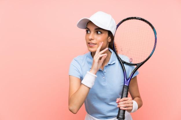 Giovane donna del tennis sopra la parete rosa isolata che bisbiglia qualcosa