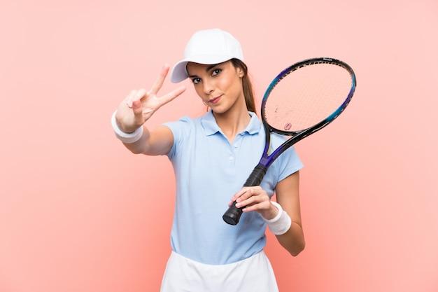 Giovane donna del tennis sopra la parete rosa isolata che sorride e che mostra il segno di vittoria