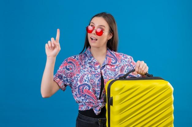 Giovane donna del viaggiatore che indossa gli occhiali da sole rossi che tengono valigia gialla con il dito su che sembra sicuro avere grande idea sopra la parete blu