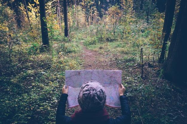 Giovane donna del viaggiatore con la mappa, alla foresta di verde di autunno nel giorno soleggiato.