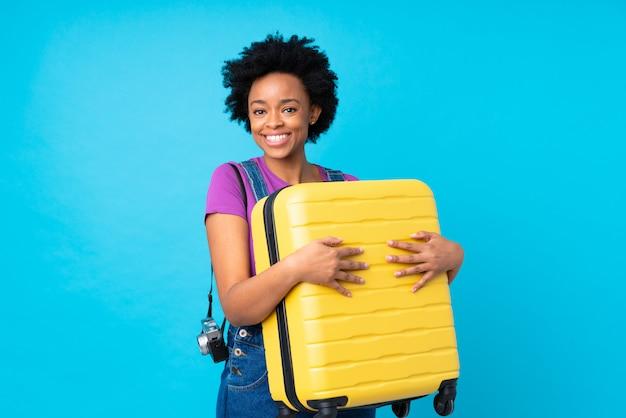Giovane donna del viaggiatore con la valigia sopra la parete isolata