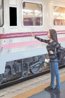 Giovane donna del viaggiatore con lo zaino che controlla destinazione dal bordo bianco del computer in bianco prima di salire sul treno