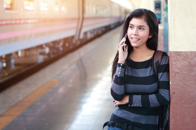 Giovane donna del viaggiatore con lo zaino facendo uso dello smart phone durante il viaggio in vacanza