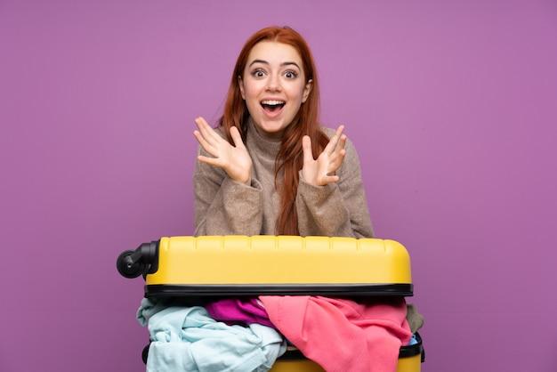 Giovane donna del viaggiatore con una valigia piena di vestiti con espressione facciale a sorpresa