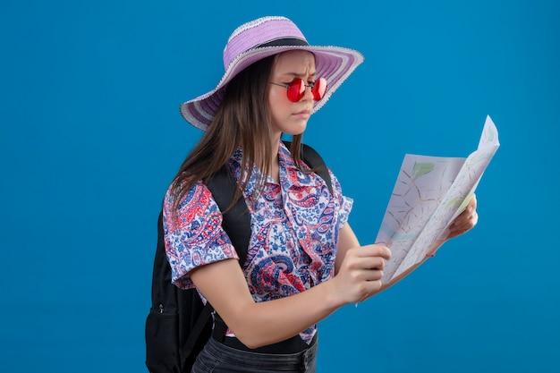 Giovane donna del viaggiatore in cappello estivo che indossa occhiali da sole rossi che tengono mappa guardandolo con il viso accigliato in piedi su sfondo blu