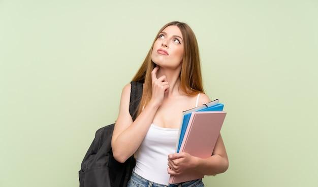 Giovane donna dell'allievo sopra fondo verde isolato che pensa un'idea