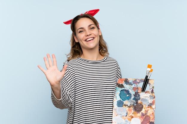 Giovane donna dell'artista che tiene una tavolozza sopra il saluto blu isolato con la mano con l'espressione felice