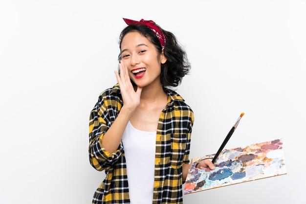 Giovane donna dell'artista che tiene una tavolozza sopra la parete bianca isolata che grida con la bocca spalancata