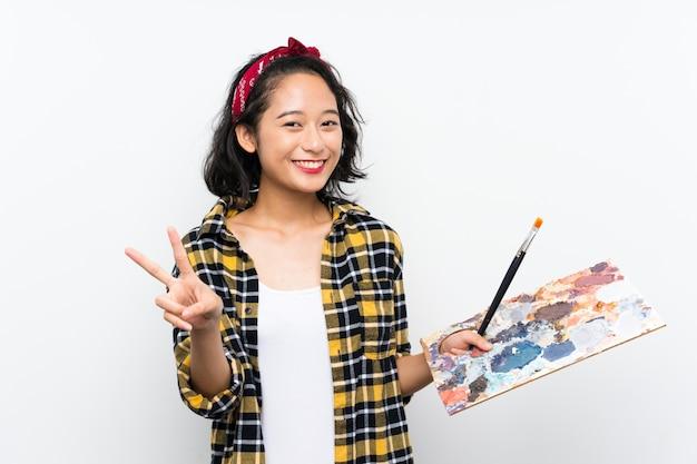 Giovane donna dell'artista che tiene una tavolozza sopra la parete bianca isolata che sorride e che mostra il segno di vittoria