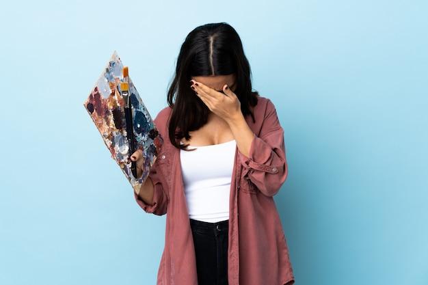 Giovane donna dell'artista che tiene una tavolozza sopra la parete blu isolata con l'espressione stanca e malata