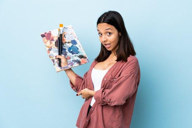Giovane donna dell'artista che tiene una tavolozza sopra le mani d'estensione blu isolate al lato per l'invito a venire