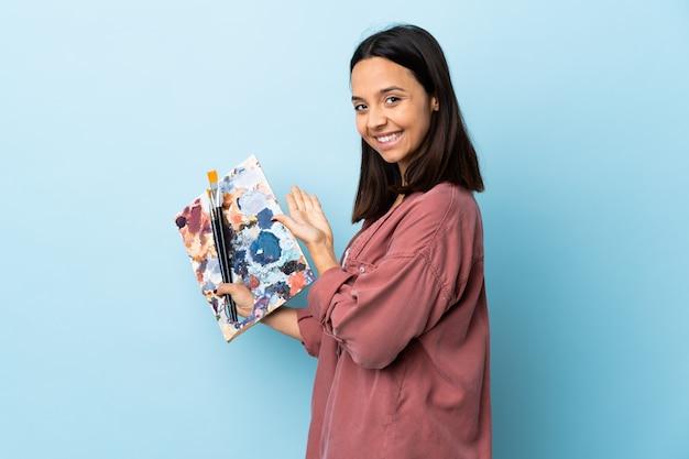 Giovane donna dell'artista che tiene una tavolozza sulle mani estendentesi isolate blu al lato per l'invito a venire
