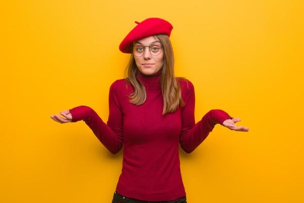 Giovane donna dell'artista francese che dubita e che scrolla le spalle le spalle