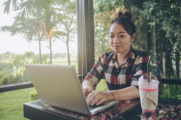 Giovane donna dell'asia che si siede da solo alla caffetteria che lavora ad un computer portatile