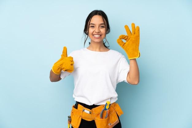 Giovane donna dell'elettricista sulla parete blu che mostra segno e pollice giusti sul gesto